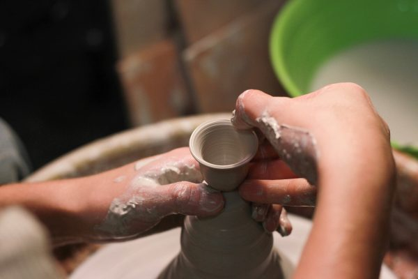 throw a clay pot on a potter's wheel