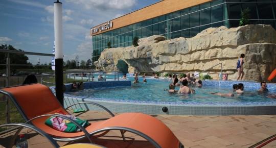 Investments: ludzie kąpiący sie w basenie, na pierwszym planie czerwony leżak
