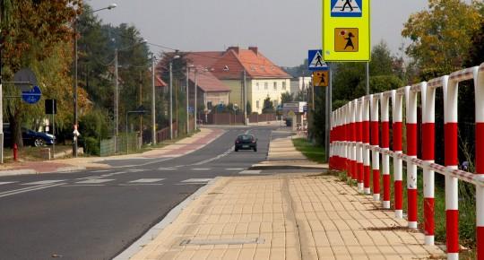 Ulica, chodnik z beżowego pozbruku, biało-czerwone barierki ochronne
